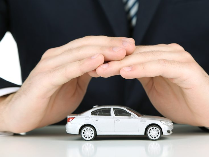 Closeup of a insurance agent covering toy car with hands on table